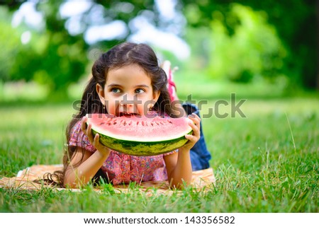 Cute hispanic girl eating watermelon at park