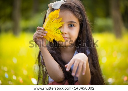 Cute hispanic little girl  hiding over yellow leaf - stock photo