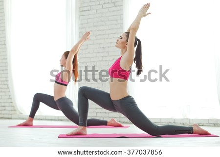Cute Hispanic women practicing the cobra pose during their yoga class in a gym - stock photo