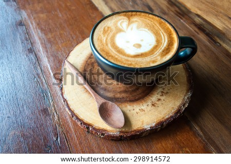 Cute Hot Cappuccino Coffee on wooden saucer with natural light from window - stock photo