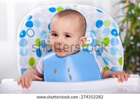 Cute hungry kid making mess - stock photo