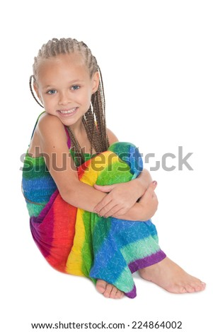 Cute in a colorful dress sitting on the floor. Girl six years. - stock photo