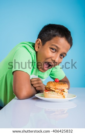 cute indian boy eating burger, small asian boy and burger, over blue background - stock photo