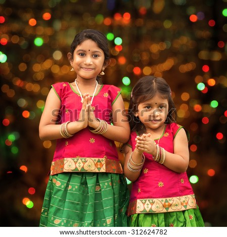 Cute Indian girls dressed in sari with folded hands representing traditional Indian greeting, standing inside a temple celebrating diwali, festival of lights. - stock photo