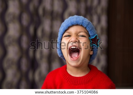 Cute Indian Kid striking a pose wearing red sweater and blue cap with a big laugh available with clipping path - stock photo