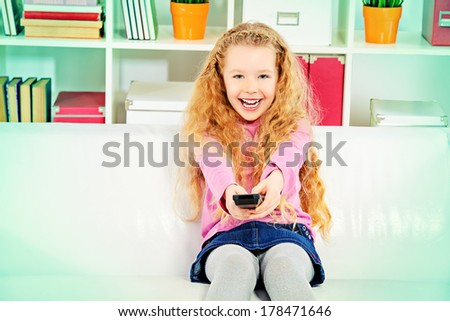 Cute joyful girl sitting on a sofa at home with a TV remote and watching TV. - stock photo