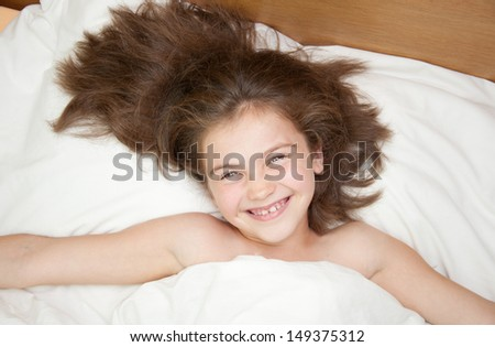 Cute just awaked girl inb the bed. - stock photo