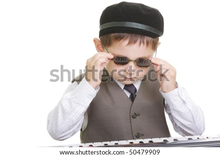Cute kid adjusting spectacles at piano keyboard against white background