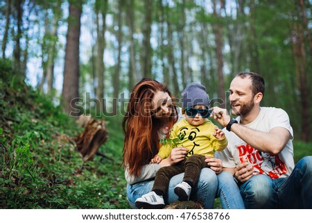 Cute kid and his parents sitting on a tree branch
