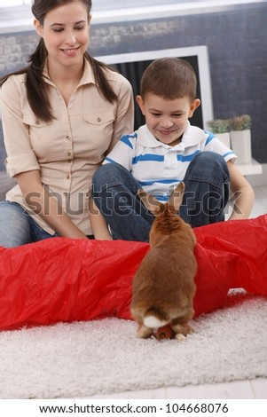 Cute kid and mom playing with pet rabbit on living room floor, smiling.
