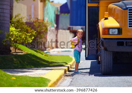 cute kid are getting on the bus, ready to go to school - stock photo