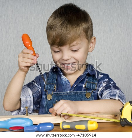 Cute kid as a construction worker, playing with tools - stock photo