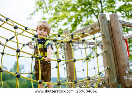 Cute kid boy having fun with climbing on children playground, outdoors, on warm summer day. - stock photo