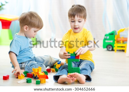 Cute kid boy playing with little brother at home - stock photo