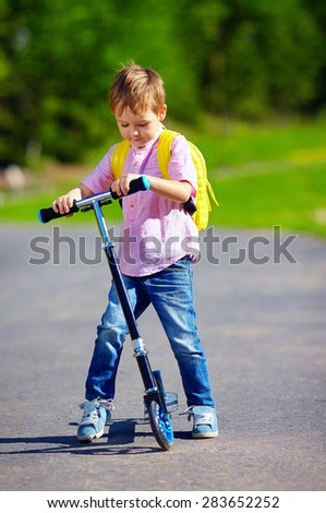 cute kid boy riding a scooter on the road, summer outdoors