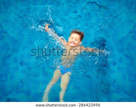cute kid, boy swimming in pool water, top view