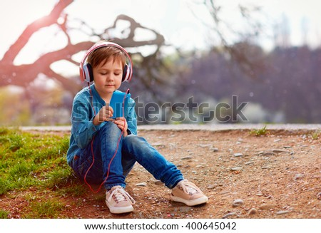 cute kid boy with headphones listens to the music in  park - stock photo