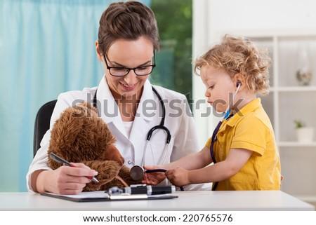 Cute kid diagnosing teddy bear at pediatrician - stock photo