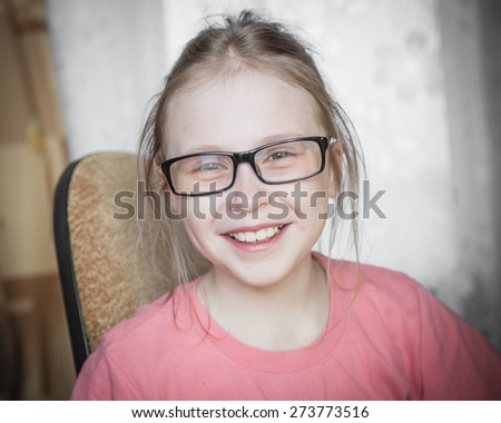 Cute kid girl at home while wearing glasses.