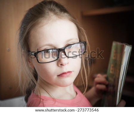 Cute kid girl at home while wearing glasses. - stock photo