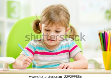 cute kid girl drawing with colourful pencils - stock photo
