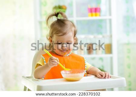 cute kid girl eating food on kitchen - stock photo