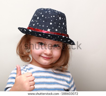 Cute kid girl in blue hat showing thumb up sign - stock photo