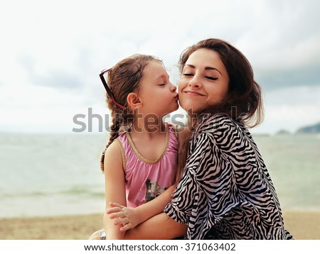 Cute kid girl kissing her happy enjoying mother with closed eyes and natural emotion on sea background