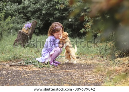 Cute kid girl petting the red cat in spring garden - stock photo