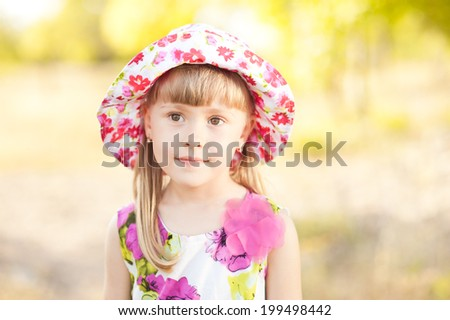 Cute kid girl posing outdoors, wearing summer clothes on nature background - stock photo