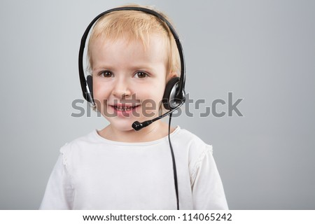 Cute kid girl talking to customers as a consultant call center using headset.  Girl is working as an operator at helpline. Gray background. Studio shot. - stock photo