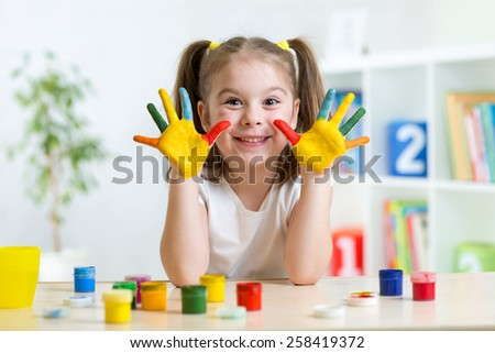 cute kid girl  with hands painted in colorful paints in nursery - stock photo