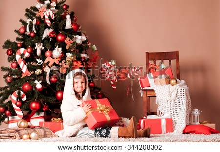 Cute kid girl 4-5 year old holding christmas presents under christmas tree in room. Looking at camera. Childhood. Holding gifts. Christmas celebration.  - stock photo