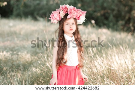 Cute kid girl 4-5 year old wearing stylish peony hairband outdoors. Looking at camera. Childhood.  - stock photo