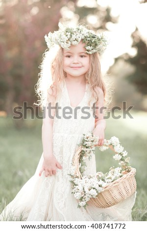 Cute kid girl 4-5 year old with basket of flowers wearing floral wreath outdoors. Looking at camera. Childhood. Wedding day. - stock photo
