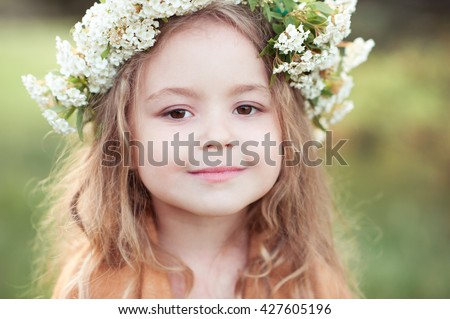 Cute kid girl 4-5 year old with flowers in hairstyle outdoors. Looking at camera. Childhood.  - stock photo