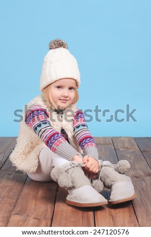 Cute kid girl 3-4 years old posing over blue. Wearing trendy winter knitted clothes. Sitting on wooden floor. Looking at camera. - stock photo