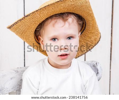 Cute kid in cowboy straw hat - stock photo