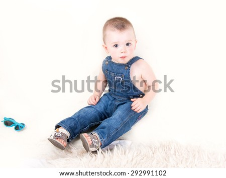 Cute kid in denim overalls with sunglasses sitting isolated on white background