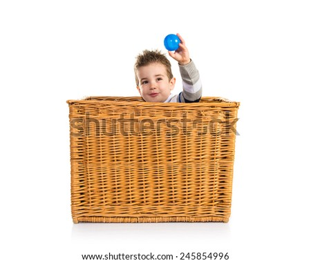 Cute kid inside basket playing with blue balls