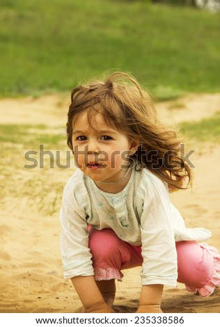Cute kid is playing and sitting on send in sunny day - stock photo