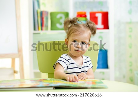cute kid little girl with a book indoors