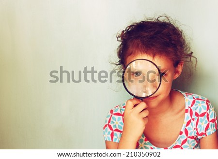 cute kid looking through magnifying glass . - stock photo