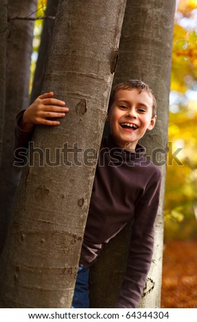 Cute kid playing outdoor in a beautiful autumn day - stock photo