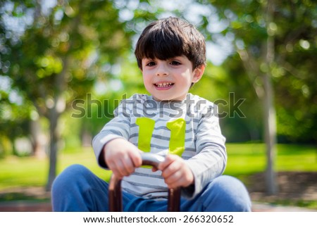 Cute kid plays in the playground - stock photo