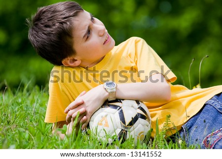 Cute kid resting in meadow after soccer game - stock photo