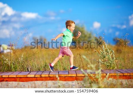 cute kid running the summer field - stock photo