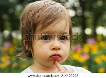Cute kid thinking at the park - stock photo