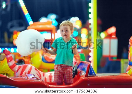 cute kid with cotton candy on carousel - stock photo
