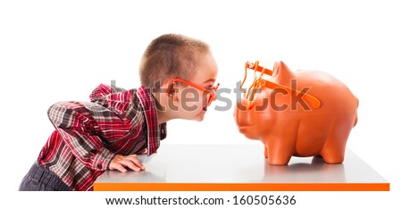Cute kid with sunglasses playing with piggy bank - stock photo